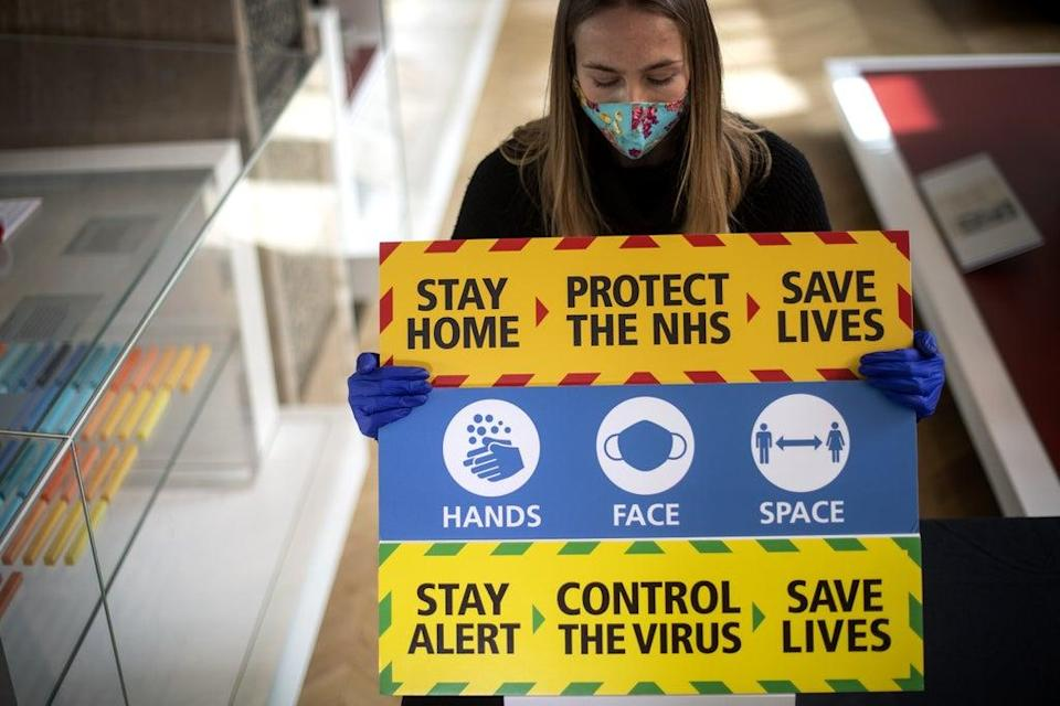 A staff member holds three signs from the Downing Street briefings (PA) (PA Archive)