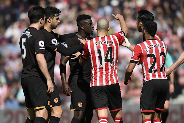 <p>Hull City's Oumar Niasse is held back by Harry Maguire as Southampton's Oriol Romeu looks on </p>