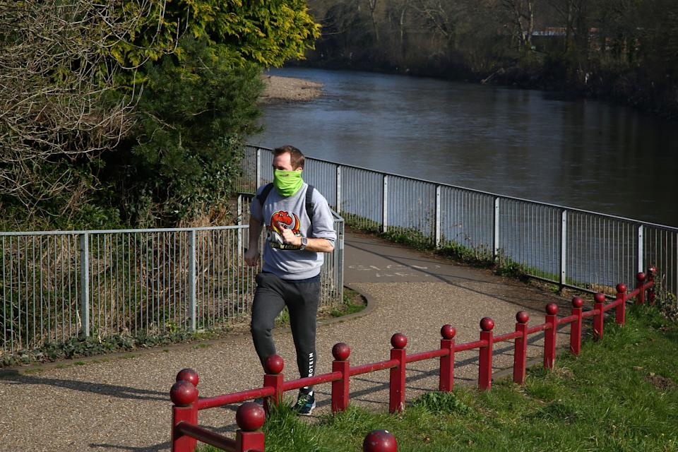 """A jogger exercises in a park in Cardiff, south Wales on the morning on March 24, 2020 after Britain's government ordered a lockdown to slow the spread of the novel coronavirus. - Britain was under lockdown March 24, its population joining around 1.7 billion people around the globe ordered to stay indoors to curb the """"accelerating"""" spread of the coronavirus. (Photo by GEOFF CADDICK / AFP) (Photo by GEOFF CADDICK/AFP via Getty Images)"""