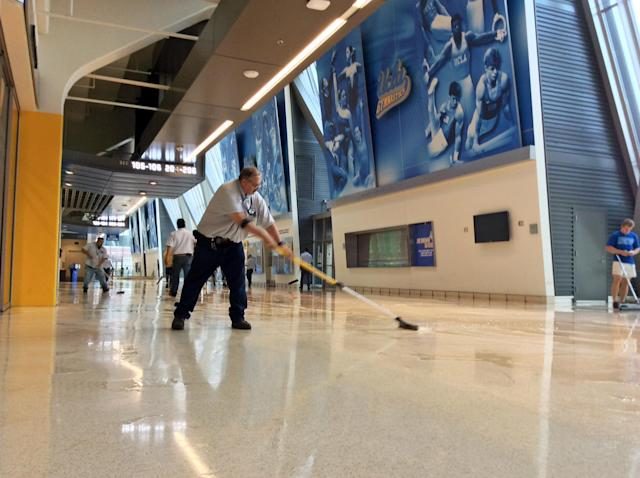 A worker clears water from the lobby floor of Pauley Pavilion, home of UCLA basketball, after a 30-inch water main burst on nearby Sunset Boulevard Tuesday, July 29, 2014, in Loss Angeles. Water also reached the playing floor of the basketball arena. (AP Photo/Matt Hamilton)