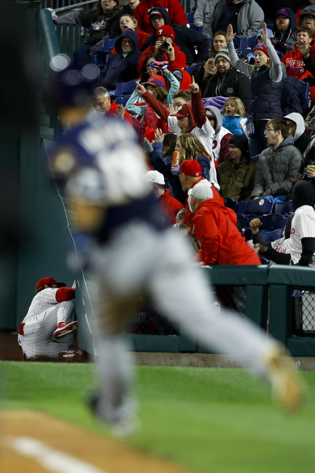 Philadelphia Phillies right fielder Bryce Harper, left, collides with the wall after catching a pop-foul by Milwaukee Brewers' Keston Hiura, right, during the sixth inning of a baseball game, Tuesday, May 14, 2019, in Philadelphia. Milwaukee won 6-1.(AP Photo/Matt Slocum)