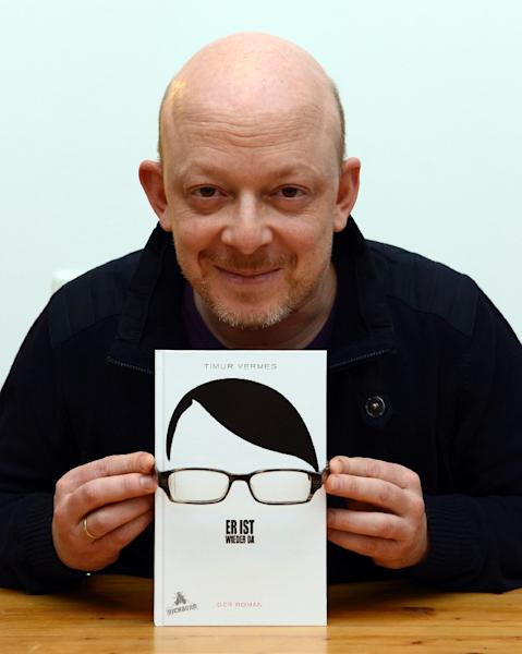 """German book writer Timur Vermes poses with his new book """"Er ist wieder da"""" in his flat in Munich, southern Germany, on January 18, 2013 (AFP Photo/Christof Stache)"""