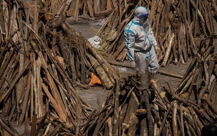 A man wearing PPE walks between funeral pyres before a mass cremation - Anindito Mukherjee/Getty Images