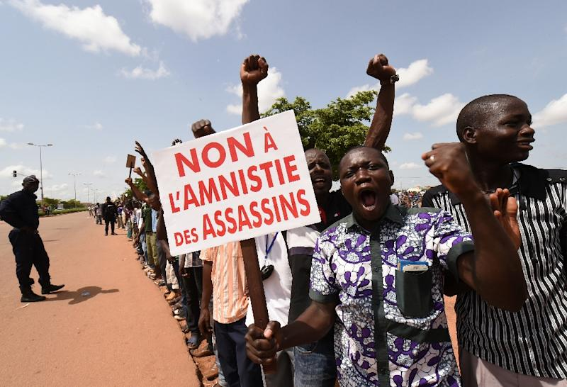 """Protesters shout slogans while holding a sign reading """"No to an amnesty for assassins"""" during a demonstration against the coup leaders (AFP Photo/Sia Kambou)"""