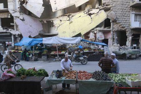 Civilians shop for vegetables and fruits displayed in front of a damaged building in Aleppo's Bustan al-Qasr neighborhood, Syria October 14, 2015. REUTERS/Hosam Katan