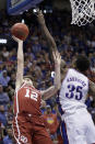Kansas center Udoka Azubuike (35) blocks a shot by Oklahoma guard Austin Reaves (12) during the second half of an NCAA college basketball game in Lawrence, Kan., Saturday, Feb. 15, 2020. Kansas defeated Oklahoma 87-70. (AP Photo/Orlin Wagner)