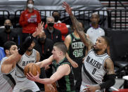 Boston Celtics guard Payton Pritchard, center, drives to the basket on Portland Trail Blazers center Enes Kanter, right, and guard Damian Lillard, right, during the first half of an NBA basketball game in Portland, Ore., Tuesday, April 13, 2021. (AP Photo/Steve Dykes)