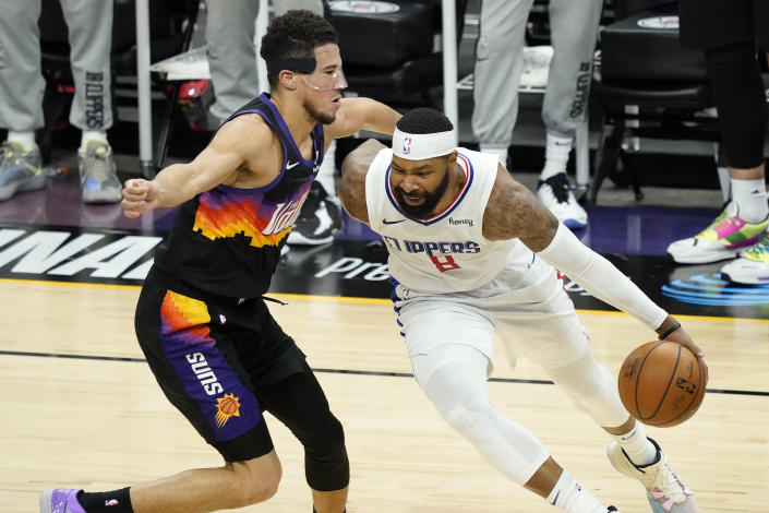 Los Angeles Clippers forward Marcus Morris Sr. (8) drives as Phoenix Suns guard Devin Booker defends during the second half of game 5 of the NBA basketball Western Conference Finals, Monday, June 28, 2021, in Phoenix. (AP Photo/Matt York)
