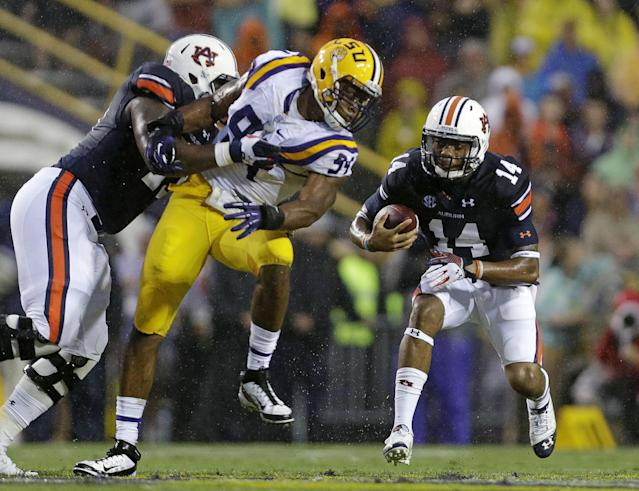 Auburn quarterback Nick Marshall (14) tries to carry around LSU defensive end Danielle Hunter (94) in the first half of an NCAA college football game in Baton Rouge, La., Saturday, Sept. 21, 2013. (AP Photo/Gerald Herbert)