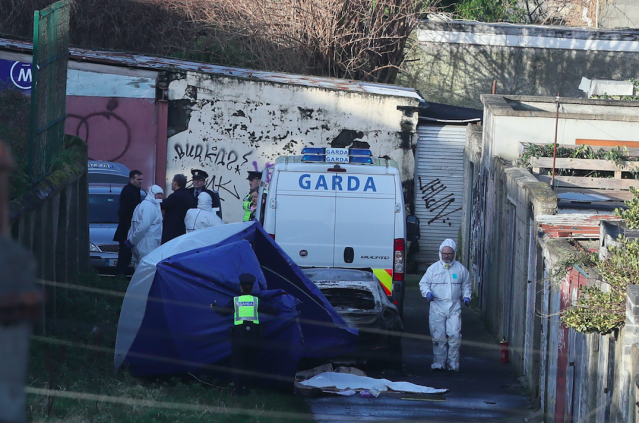 Forensic officers comb the scene for clues. (PA)