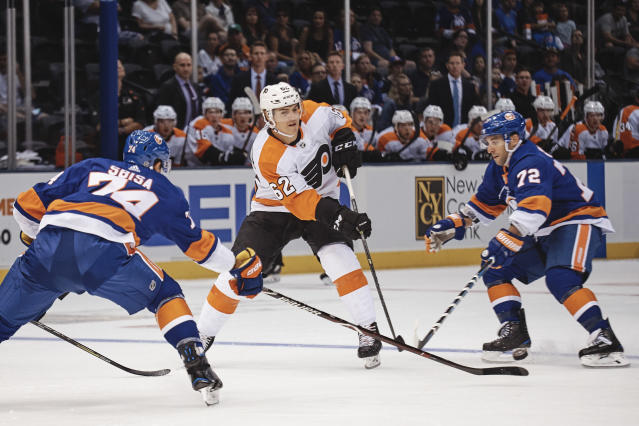 New York Islanders' Luca Sbisa, left, and Stephen Gionta, right, go for the puck against Philadelphia Flyers' Nicolas Aube-Kubel, during the first period of a preseason NHL hockey game in New York, Sunday, Sept. 16, 2018. (AP Photo/Andres Kudacki)