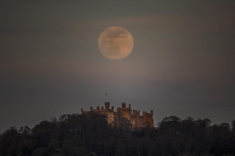 "A pink supermoon is seen over Belvoir castle in Leicestershire, England, Tuesday, April 7, 2020. The phenomenon of ""supermoon'' happens when the moon is at its closest point to the earth and looks larger than usual. (Danny Lawson/PA via AP)"