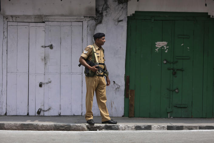 """An Indian paramilitary soldier stands guard near closed shops in Jammu, India, Tuesday, Aug.6, 2019. India's lower house of Parliament was set to ratify a bill Tuesday that would downgrade the governance of India-administered, Muslim-majority Kashmir amid an indefinite security lockdown in the disputed Himalayan region. The Hindu nationalist-led government of Prime Minister Narendra Modi moved the """"Jammu and Kashmir Reorganization Bill"""" for a vote by the Lok Sahba a day after the measure was introduced alongside a presidential order dissolving a constitutional provision that gave Kashmiris exclusive, hereditary rights. (AP Photo/Channi Anand)"""