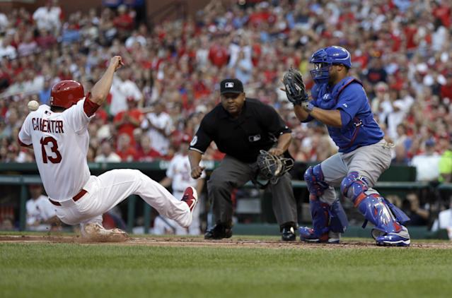 St. Louis Cardinals' Matt Carpenter, left, is safe at home as he is hit in the back by the throw as Chicago Cubs catcher Welington Castillo, right, and home plate umpire Adrian Johnson, center, watch during the first inning of a baseball game on Wednesday, June 19, 2013, in St. Louis. (AP Photo/Jeff Roberson)