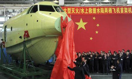 Officials of Aviation Industry Corporation of China (AVIC) unveil the newly-made nose of amphibious aircraft AG600, during a ceremony at a factory in Chengdu