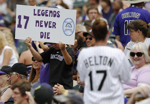Fans hold up placards for retired Colorado Rockies first baseman Todd Helton before his number was retired in a ceremony before the Rockies baseball game with the Cincinnati Reds in Denver on Sunday, Aug. 17, 2014. (AP Photo/David Zalubowski)