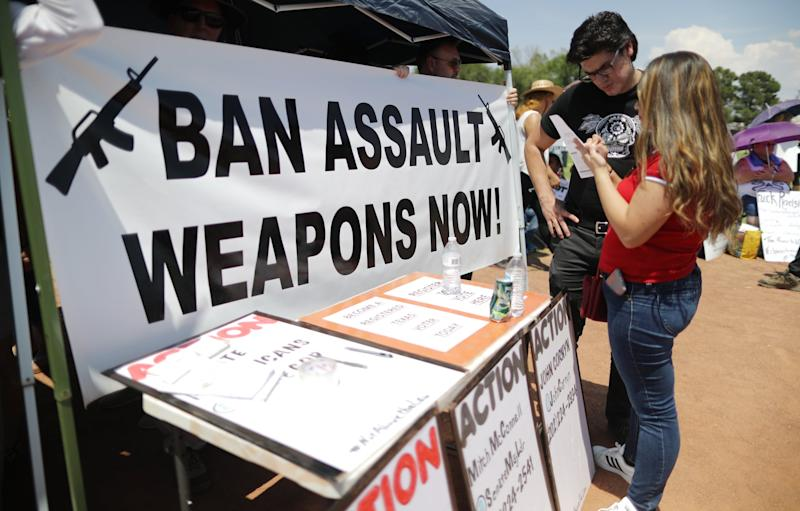 EL PASO, TEXAS - AUGUST 07: A 'Ban Assault Weapons Now' sign is displayed near a voter registration table at a protest against President Trump's visit, following a mass shooting which left at least 22 people dead, on August 7, 2019 in El Paso, Texas. Protestors also called for gun control and denounced white supremacy. A 21-year-old white male suspect remains in custody in El Paso which sits along the U.S.-Mexico border. (Photo by Mario Tama/Getty Images)