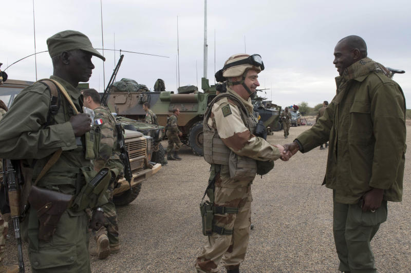 In this picture taken on Monday, Jan. 28, 2013, provided by the French Army Communications Audiovisual office (ECPAD) and released Tuesday, Jan. 29, 2013, a French soldier, second from right, shakes hands with a resident of Timbuktu, north Mali. Backed by French helicopters and paratroopers, Malian soldiers entered the fabled city of Timbuktu on Monday after al-Qaida-linked militants who ruled the outpost by fear for nearly 10 months fled into the desert, setting fire to a library that held thousands of manuscripts dating to the Middle Ages.(AP Photo/French Army Communications Audiovisual office (ECPAD), Arnaud Roine)