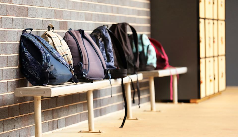 A number of school bags back packs leaning against a brick wall with lockers blurred in the background. School yard, playground, high school eduicational facility. No students