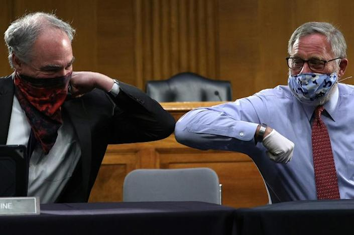 US Senators Tim Kaine (L) and Richard Burr greet each other with an elbow bump before a Senate committee hearing on the coronavirus epidemic (AFP Photo/Win McNamee)