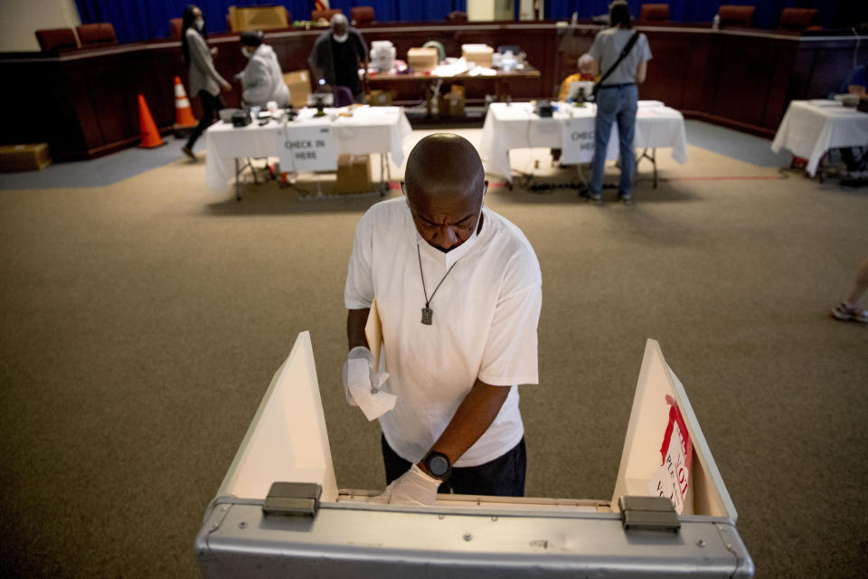Darren Atkinson wears a mask as he wipes down a voting booth at a voting center during primary voting in Washington, Tuesday, June 2, 2020. (AP Photo/Andrew Harnik)
