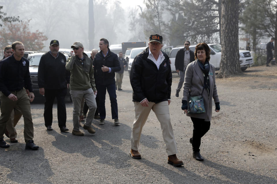 FILE - In this Nov. 17, 2018, file photo, President Donald Trump talks to Mayor Jody Jones as he visits a neighborhood impacted by the wildfires, in Paradise, Calif. Jones' home was one of nearly 9,000 homes destroyed in the deadliest and most destructive wildfire in California history. (AP Photo/Evan Vucci, File )