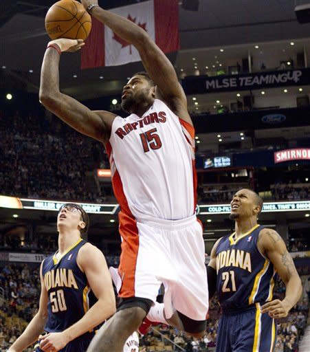 Toronto Raptors' Amir Johnson (15) scores as Indiana Pacers Tyler Hansbrough (50) and David West look on during first half NBA basketball action in Toronto, Friday, Jan. 13, 2012. (AP Photo/The Canadian Press, Chris Young)