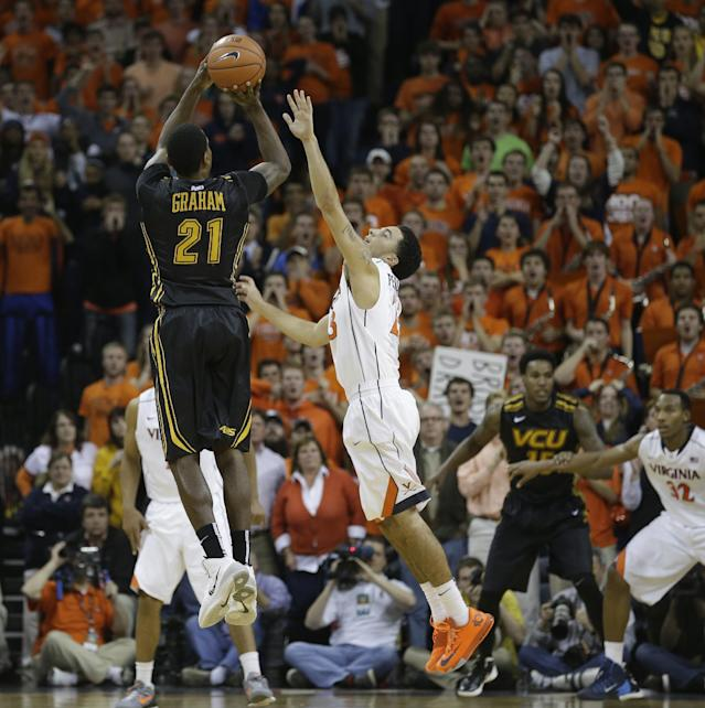 Virginia Commonwealth guard Treveon Graham (21) launches a winning three-point shot over Virginia guard London Perrantes (23) during the second half of an NCAA college basketball game in Charlottesville, Va., Tuesday, Nov. 12, 2013. VCU won the game 59-56. (AP Photo/Steve Helber)