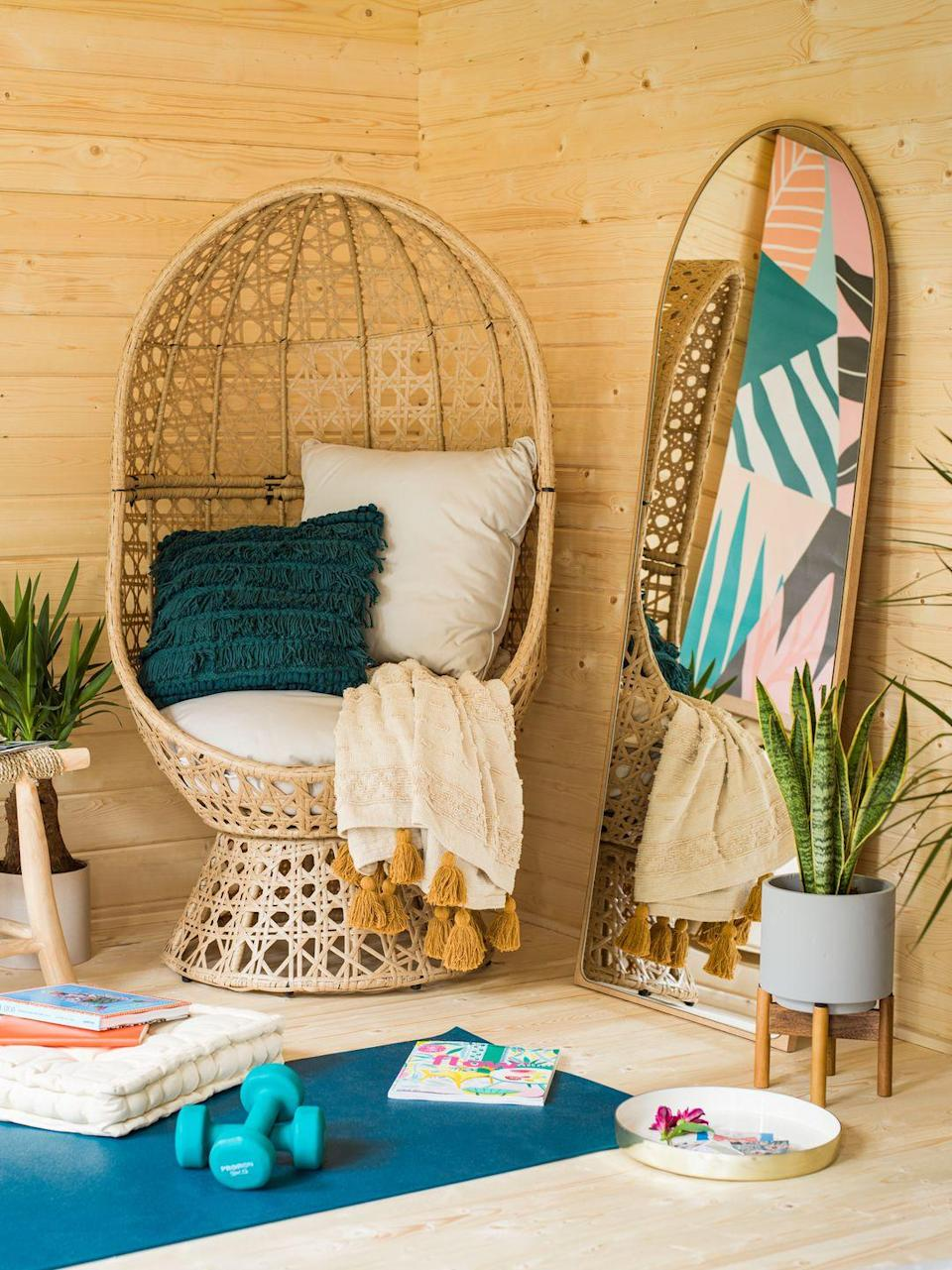"""<p>AJ loves the calming nature of the summer house, especially the cosy 'wellness corner' where she's able to relax in the statement rattan balloon chair, which she says is her favourite piece of furniture. </p><p>A <a href=""""https://go.redirectingat.com?id=127X1599956&url=https%3A%2F%2Fwww.wayfair.co.uk%2Fhome-decor%2Fpdp%2Fbrayden-studio-crewkerne-full-length-mirror-u000981097.html&sref=https%3A%2F%2Fwww.housebeautiful.com%2Fuk%2Fgarden%2Fg36462362%2Faj-odudu-garden-summer-house%2F"""" rel=""""nofollow noopener"""" target=""""_blank"""" data-ylk=""""slk:full-length mirror"""" class=""""link rapid-noclick-resp"""">full-length mirror</a> leaning against the wall makes the space look bigger and brighter by reflecting the sunlight streaming in through the floor-to-ceiling windows. <br></p>"""