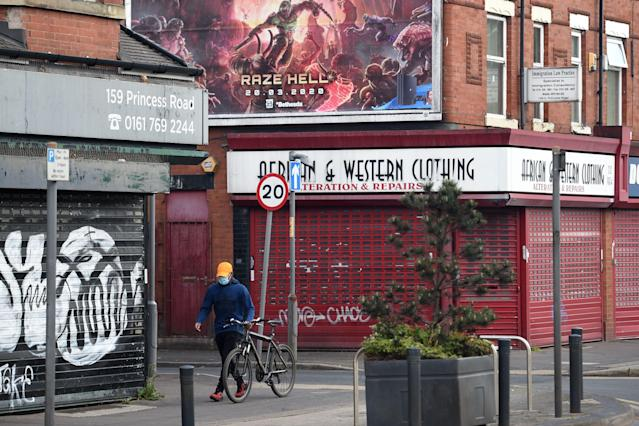 A man wearing a face mask wheels his bicycle past shuttered shops in Manchester, England, on 11 May. (Oli Scarff / AFP via Getty Images)