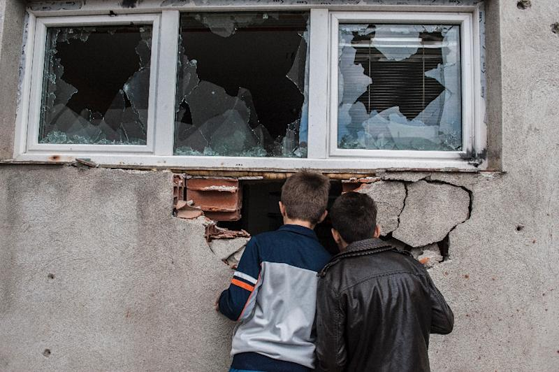 Boys look through a hole in a destroyed house after fighting in Kumanovo on May 11, 2015 (AFP Photo/Armend Nimani)
