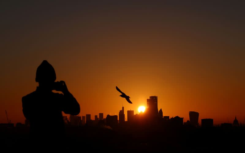 FILE PHOTO: A person takes a photograph of the London skyline from Primrose Hill