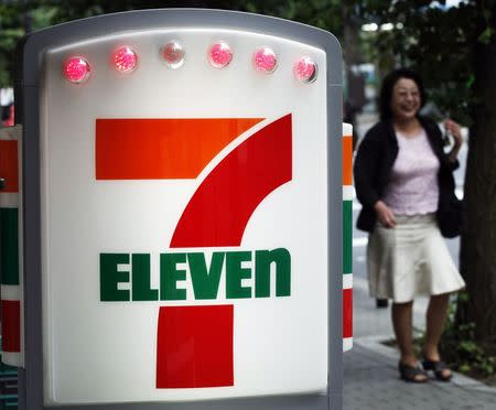 A woman walks past a signboard of convenience store chain, Seven-Eleven in Tokyo, in this file picture taken July 7, 2011.   REUTERS/Kim Kyung-Hoon/Files