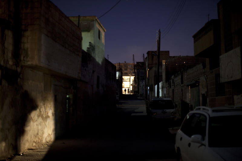 People are silhouetted at the end of a road in the old city of Idlib, north Syria, Monday, March 5, 2012. Syrian refugees fleeing to neighboring Lebanon on Monday said they feared they would be slaughtered in their own homes as government forces hunted down opponents in a brutal offensive against the opposition stronghold of Homs. (AP Photo/Rodrigo Abd)