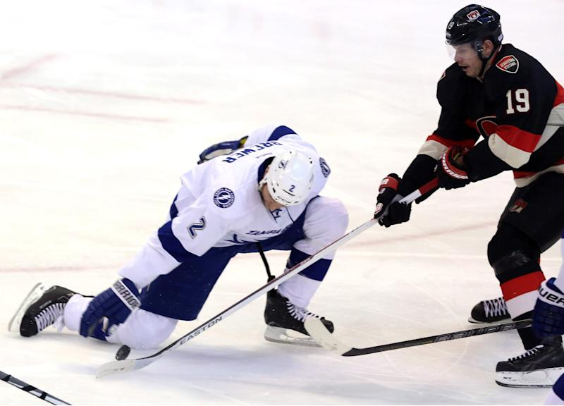 Tampa Bay Lighting's Eric Brewer (2) attempts to move the puck with his glove after losing his stick as Ottawa Senators' Jason Spezza (19) defends during the the first period of an NHL hockey game, Thursday, Jan. 30, 2014 in Ottawa, Ontario. (AP Photo/The Canadian Press, Fred Chartrand)