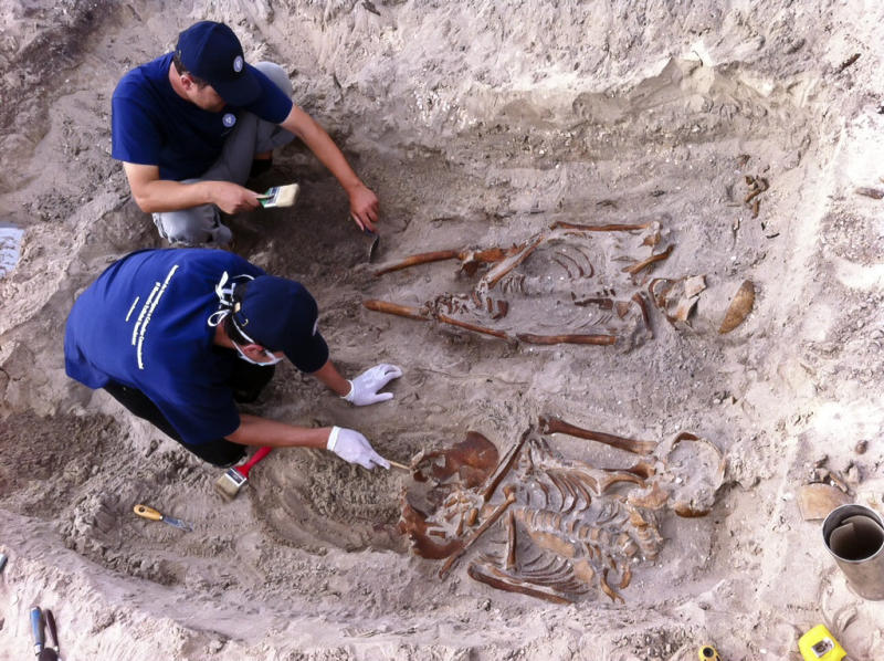 "FILE In this Monday Sept. 16, 2013 file image provided by the Institute for the Investigation of Communist Crimes, investigators work around human remains at a grave site near the Periprava former communist labor camp in the Danube Delta region, eastern Romania. Authorities on Tuesday, Oct. 1, 2013, confirmed the existence of a mass grave near the site of a former communist labor camp in eastern Romania. The discovery bolsters the case of investigators seeking genocide charges against the former commander of the labor camp. A statement from the government's Institute for Investigating the Crimes of Communism said five skeletons were found _ one's right foot was missing, one had a dislocated spine and another's legs were tied together. Institute chief Andrei Muraru said the finding revealed ""brutality and primitivism in the management of the colony."" (AP Photo/ Institute for the Investigation of Communist Crimes, File )"