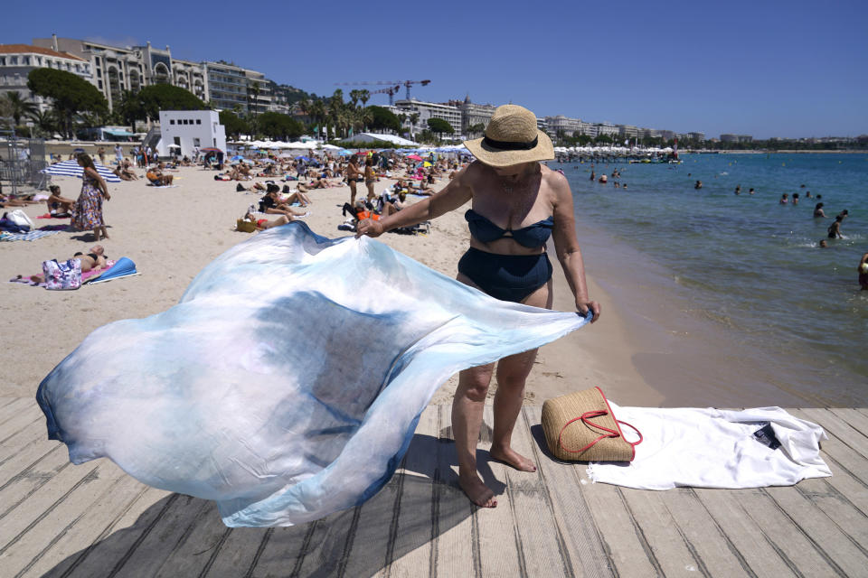A member of the public prepares to sit on the beach ahead of the 74th international film festival, Cannes, southern France, July 5, 2021. The Cannes film festival runs from July 6 - July 17, 2021. (AP Photo/ Brynn Anderson)