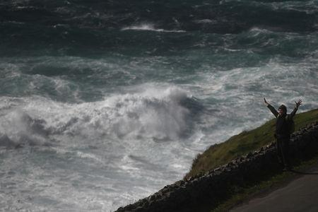 A man looks out at rough sea from Slea Head during Storm Ali in Coumeenoole Ireland