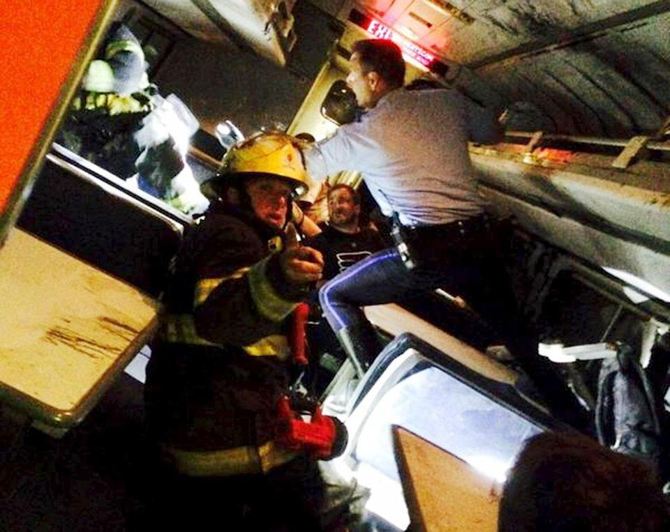 A rescuer searches for injured people inside the derailed Amtrak train in Philadelphia May 12, 2015 in a photo provided by former Pennsylvania Congressman Patrick Murphy, who was a passenger on the train. An Amtrak passenger train with more than 200 passengers on board derailed in north Philadelphia on Tuesday night, killing at least five people and injuring scores of others, several of them critically, authorities said. Picture taken May 12, 2015. REUTERS/@PatrickMurphyPA/Handout via Reuters ATTENTION EDITORS - THIS PICTURE WAS PROVIDED BY A THIRD PARTY. REUTERS IS UNABLE TO INDEPENDENTLY VERIFY THE AUTHENTICITY, CONTENT, LOCATION OR DATE OF THIS IMAGE. THIS PICTURE WAS PROCESSED BY REUTERS TO ENHANCE QUALITY. AN UNPROCESSED VERSION WILL BE PROVIDED SEPARATELY. FOR EDITORIAL USE ONLY. NOT FOR SALE FOR MARKETING OR ADVERTISING CAMPAIGNS. NO SALES. NO ARCHIVES. NO COMMERCIAL USE.