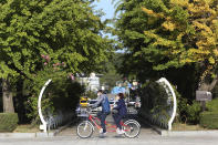 A couple wearing face masks to help protect against the spread of the coronavirus rides a bicycle at a park in Goyang, South Korea, Tuesday, Oct. 6, 2020. (AP Photo/Ahn Young-joon)