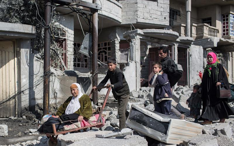 A family walk past buildings destroyed by coalition airstrikes in the neighbourhood of Sammod, on the southern edge of western Mosul on March 9 - Credit: Sam Tarling / The Telegraph