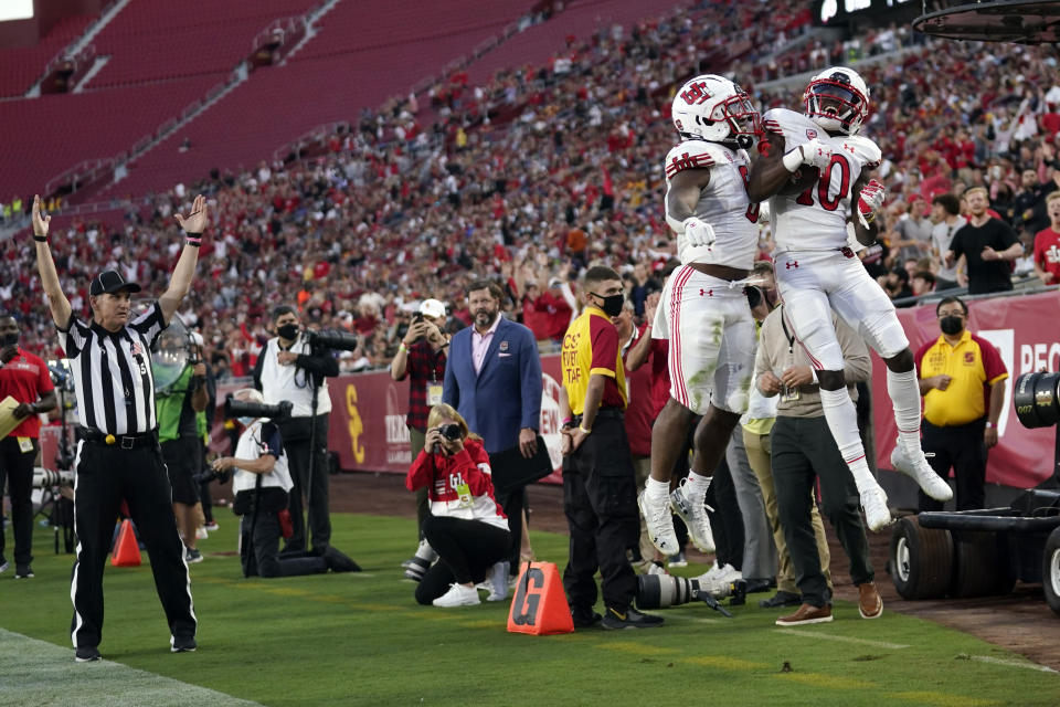 Utah wide receiver Money Parks (10) celebrates his touchdown reception with running back TJ Pledger during the first half of the team's NCAA college football game against Southern California on Saturday, Oct. 9, 2021, in Los Angeles. (AP Photo/Marcio Jose Sanchez)