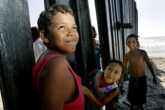 Young Mexican nationals peer through the border wall at the beach along San Ysidro, California.