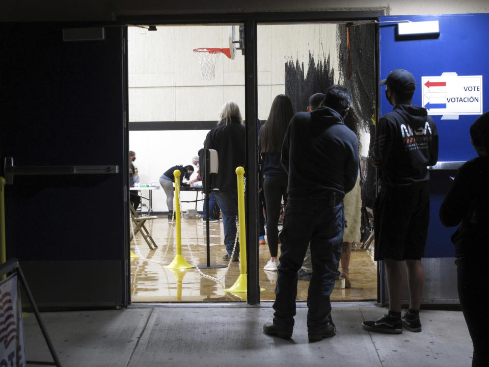 FILE - In this Nov. 3, 2020, file photo, some of the last voters wait in line to cast their ballots after the line was cut off at 7 p.m., local time, outside the gymnasium at Reed High School in Sparks, Nev. Everyone in line when the polls closed at 7 p.m. was allowed to vote in Washoe County, where registration is split evenly between the two major parties in the northern part of the state. A new survey measuring the popularity of major pieces of sweeping legislation in Congress finds solid support from Americans for Democrats' proposals to overhaul voting in the U.S. The Associated Press-NORC Center for Public Affairs Research poll found about half of Americans support expanding access to early and mail voting, while about 3 in 10 opposed the ideas and the rest had no opinion. (AP Photo/Scott Sonner, File)