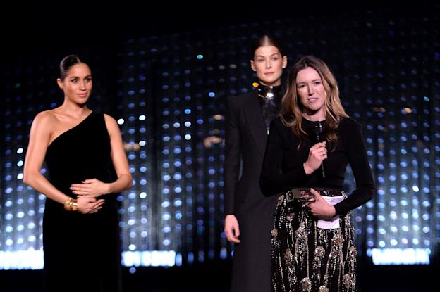 LONDON, ENGLAND - DECEMBER 10: Clare Waight Keller is watched by Meghan, Duchess of Sussex and Rosamund Pike as she speaks on stage after receiving the award for British Designer of the Year Womenswear Award for Givenchy during The Fashion Awards 2018 In Partnership With Swarovski at Royal Albert Hall on December 10, 2018 in London, England. (Photo by Jeff Spicer/BFC/Getty Images)