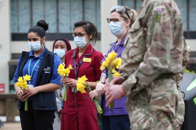 Staff and military personnel hold flowers