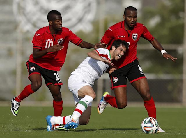 Iran's Khosrow Heidari, center, competes for the ball with Trinidad and Tobago's Kevin Molino, left, and Khaleem Hyland during the first half of an international soccer friendly at the Corinthians soccer team training center in Sao Paulo, Brazil, Sunday, June 8, 2014. Iran will play in group F of the 2014 soccer World Cup. (AP Photo/Julio Cortez)