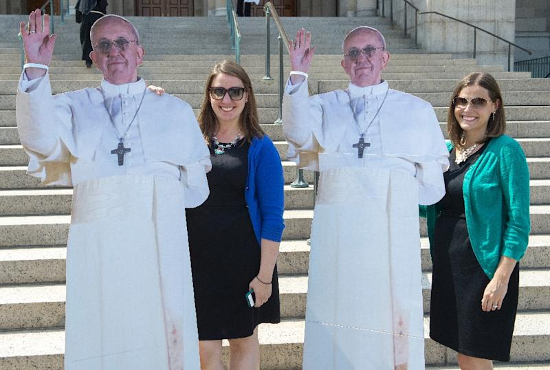 Two women have a photo taken with life-size images of Pope Francis on September 3, 2015, in Washington, DC (AFP Photo/Paul J. Richards)