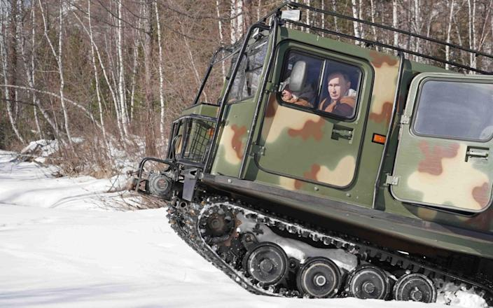 Vladimir Putin is seen behind the wheel of an all-terrain vehicle while driving through a taiga forest in Russia's Siberian Federal District