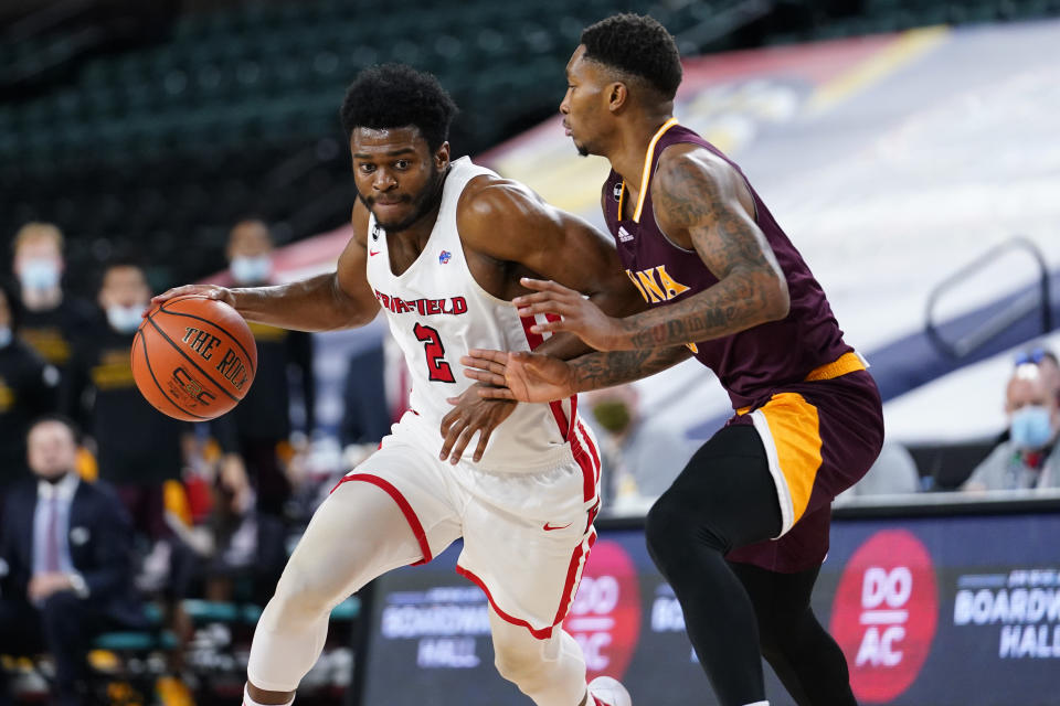Fairfield's Taj Benning, left, dribbles past Iona's Berrick JeanLouis in the second half of an NCAA college basketball game during the finals of the Metro Atlantic Athletic Conference tournament, Saturday, March 13, 2021, in Atlantic City, N.J. (AP Photo/Matt Slocum)